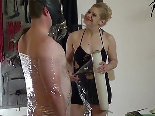 Dude is wrapped up in paper and tortured by mistress