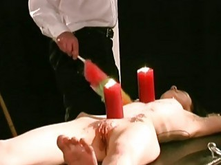 Latex submissive girl waxed, burned and pierced with big needles